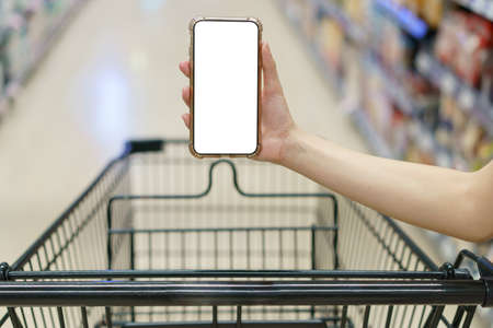Mockup, hands holding blank white screen mobile phone with shopping cart in supermarket, digital payment concept