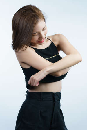 woman taking off her black shirt, side view. White background.