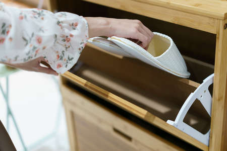 Woman opening wooden shoes storage cabinet for keep her shoes. 免版税图像