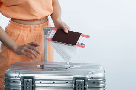 Woman hand holding face mask luggage passport and boarding pass, new normal travel concept.(Fake barcode)