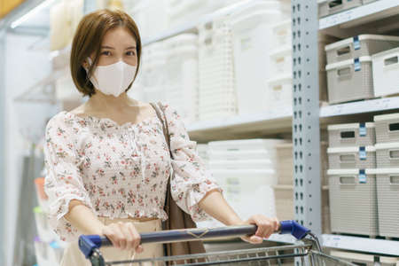 Asian woman wearing face mask push shopping cart in department store, during coronavirus or covid19 outbreak.