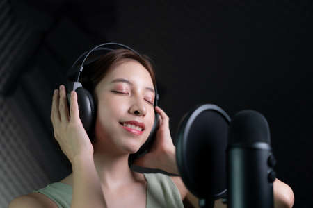 Woman recording a song or storytelling in the studio. 스톡 콘텐츠
