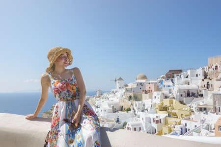 Woman tourist in flora dress visiting whitewashed village in Oia, Santorini Greece. mediterranean sea. Banco de Imagens