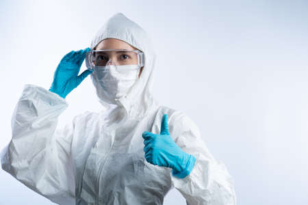 Female doctor in PPE (personal protective equipment), wearing gloves face mask and take off safety glasses.