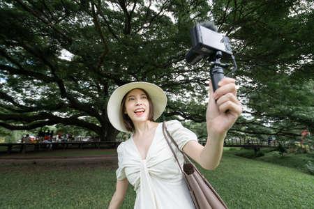 Woman wearing white dress taking selfie under the Giant Monkey Pod trees in Kanchanaburi, Thailand.
