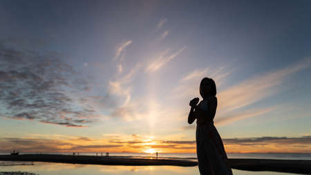 Woman and sunrise shot over the sea with beautiful cloud, sun disappeared behind a big cloud over ocean. Banco de Imagens