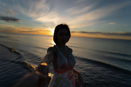 Woman and sunrise shot over the sea with beautiful cloud, sun disappeared behind a big cloud over ocean.