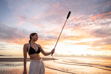 Woman in top bikini and white long pant wearing hat taking selfie with 360 camera on the beach with a beautiful sunrise or sunset