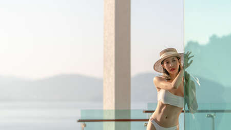 Woman in white bikini posting on the glass transparent balcony with ocean view.