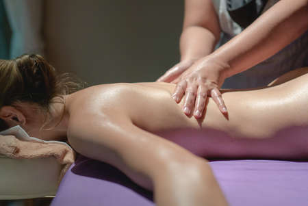 Woman lying on the massage table. relaxing back massage at spa, healing body treatment. Standard-Bild