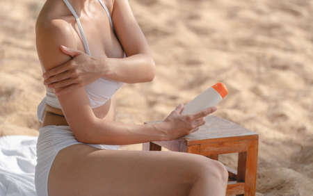 Woman on the beach applying Sunscreen while sitting on towel. Stockfoto