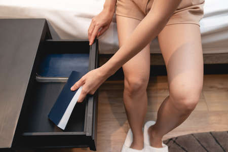 Woman sitting on bed with white sheet and next to wooden drawer stand and note book inside.