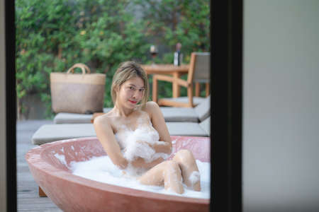 Woman playing with bubble foam while taking a bath at bathtub.