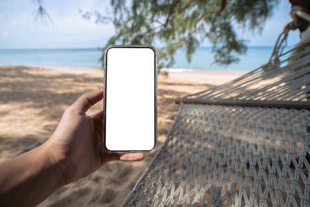 Hand holding mock up mobile with white sceen while laying on hammock swing between trees on the beach.