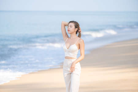 Happy young woman relax on the beach, arms raised up to sky. Stockfoto