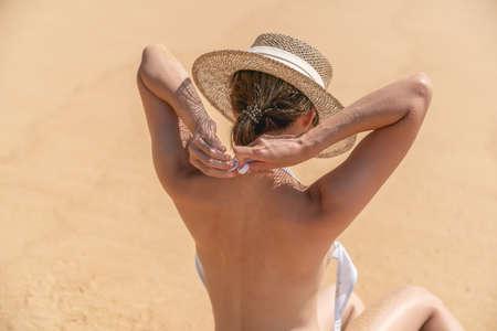 Back side woman topless sitting on sand beach relaxing sunbathing.