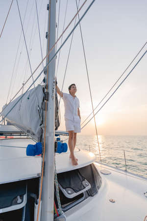 Man in white shirt standing on yacht looking at beautiful sunset.