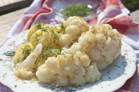 Close up photo of fresh cooked cauliflower with potatoes sprinkled with dill on wooden background.