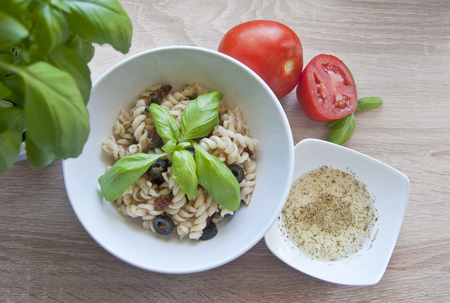 Tasty pasta with olives, dried tomatoes and herbal dressing. Decorated with basil and fresh tomatoes on wooden background. Diet meal.