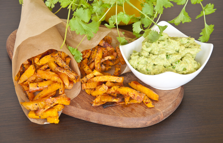 Sweet potato fries with guacamole dip decorated with fresh coriander Stock Photo