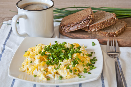 Tasty breakfast. Scrambled eggs decorated with with fresh chopped chive. Slices of dark bread, chive and coffee in the background Stock Photo