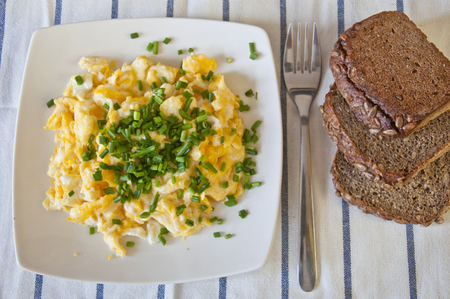 Tasty breakfast. Scrambled eggs decorated with with fresh chopped chive. Slices of dark bread and chive and in the background