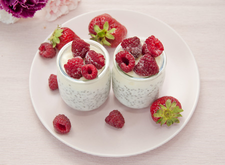 fresh natural yoghurt with sage seeds decorated with strawberries and frozen raspberries on pink background. Tasty lunch or dessert Stock Photo