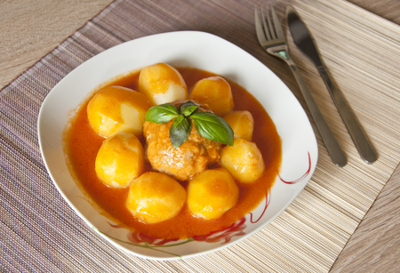 Meatball and potatoes in tomato sauce decorated with basil leaf. Closeup photo Stock Photo