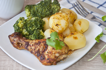 roast chicken with potatoes and broccoli decorated with coriander leaf
