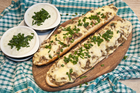 casserole with cheese and mushrooms sprinkled with fresh chive with tzatziki sauce