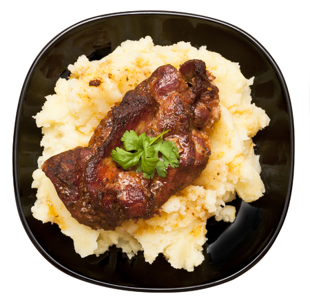 Roasted pork neck with potatoes decorated with coriander leaf isolated on white background Stock Photo