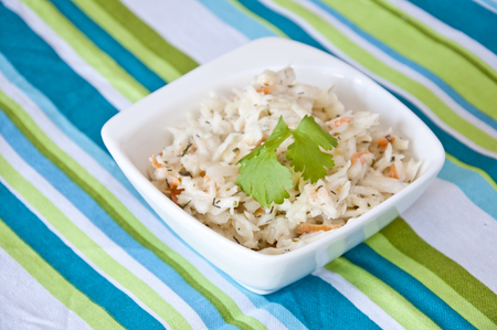 Fresh homemade leek and cabbage salad decorated with coriander leaf.