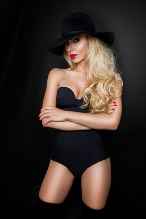 black hat: Beautiful blond woman girl sexy model dressed in black lingerie outfit body swimsuit and black hat and long boots knee Stock Photo