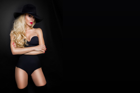 knee boots: Beautiful blond woman girl sexy model dressed in black lingerie outfit body swimsuit and black hat and long boots knee Stock Photo