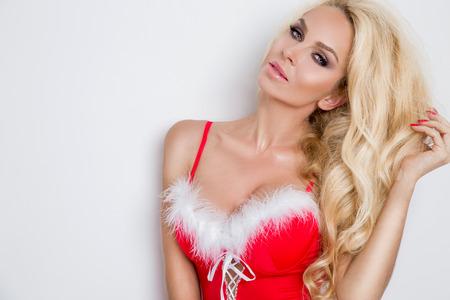 Fiocco di neve modello femminile bionda bella vestita come lingerie rossa di Babbo Natale con pelliccia bianca e calze incredibili e tacchi alti labbra sensuali trucco adorabile, foto di bellezza Natale