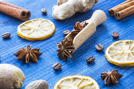 rusty background: star anise on wooden spoon with spices