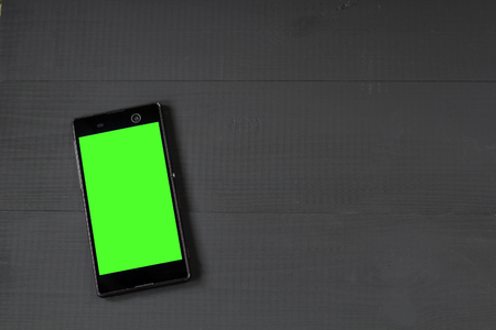 media gadget: Smart phone with green screen on wooden desk