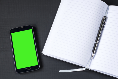 media gadget: smart phone with green screen with notepad on wooden background Stock Photo