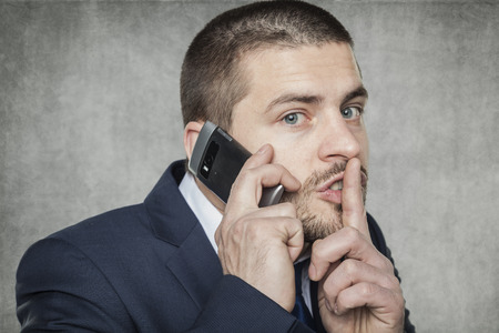 businessman talking on the phone and asks for silence photo
