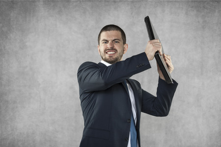 Angry businessman destroying computer Stock Photo