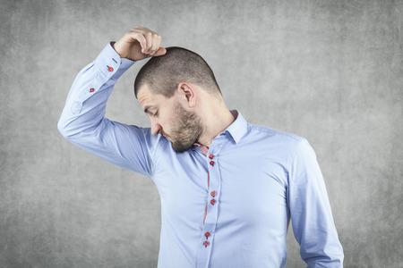 Businessman smelling his armpits