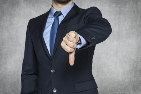 thumbs down: Businessman pointing thumbs down Stock Photo