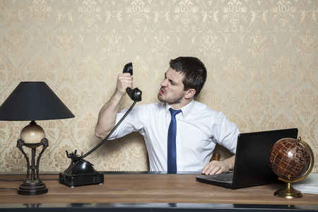 obnoxious: businessman screaming to the handset