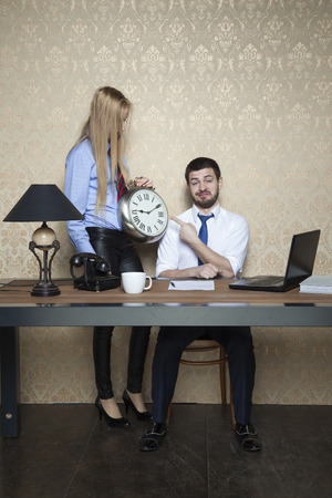 censure: businessman pointing at the clock