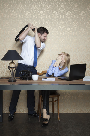 extortion: boss beats an employee for poor performance Stock Photo