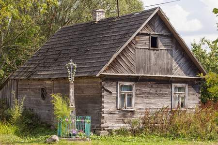 front house: old house and cross in front of building in Aleksicze Poland