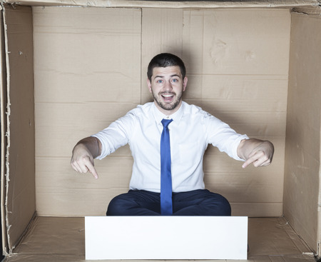 cramped space: cheerful businessman points to the copy space Stock Photo