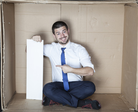 cramped space: happy businessman pointing to the copy space Stock Photo