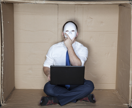 night shift: businessman wearing a mask prepares a plan Stock Photo