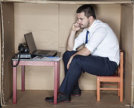 individualist: depressed businessman in a cardboard office